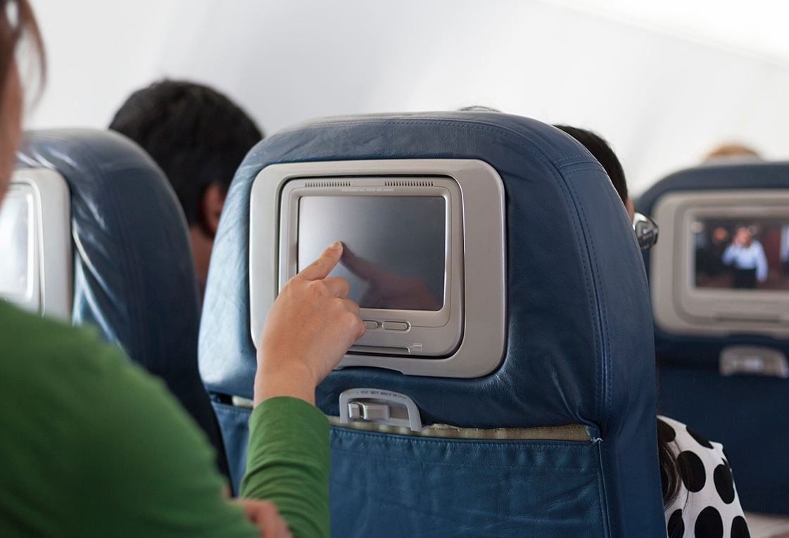 woman choosing movie on plane