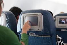 woman choosing movie on plane